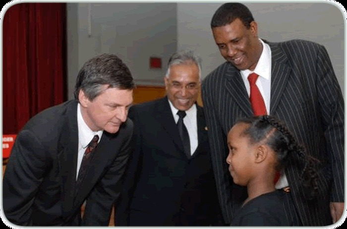 Attorney General Chris Bentley (left), Khalip Sheikh an active community supporter, and Osman Ali, president of the Somali-Canadian Association of Etobicoke (far right) greet second-grader Halima Hussein following the announcement of an Ontario government grant the association will use to benefit youth targeted by hate crimes. The association will organize a community forum to increase vigilance against hate crimes and improve support for victims.