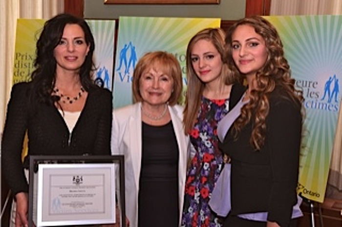 Award recipient Michelle Liotta (left) receives her award from Attorney General Madeleine Meilleur as her daughters, Josie and Cynthia Vaccaro, look on.