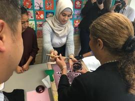 La ministre des Affaires civiques et de l'Immigration de l'Ontario Laura Albanese  et le député provincial de Trinity Spadina Han Dong créent des tees-shirts aux côtés de participants au programme d'aide à l'établissement.