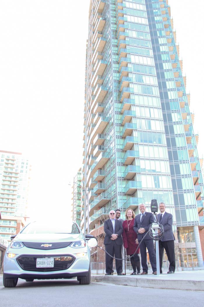 Le ministre MacCharles, le député Arthur Potts, le sous-ministre adjoint Glen Padassery, le président de l'Autorité des condominiums de l'Ontario, Tom Wright, le président de l'Autorité de réglementation de la gestion des condominiums de l'Ontario, Aubrey LeBlanc avec un véhicule électrique et une station de charge.