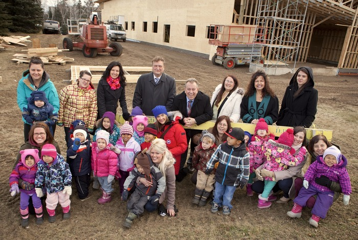 Minister Michael Gravelle (middle) announced funding for the Nanabijou Childcare Centre in Thunder Bay.  He was joined at the construction site by a group including childcare workers and children of the Centre.