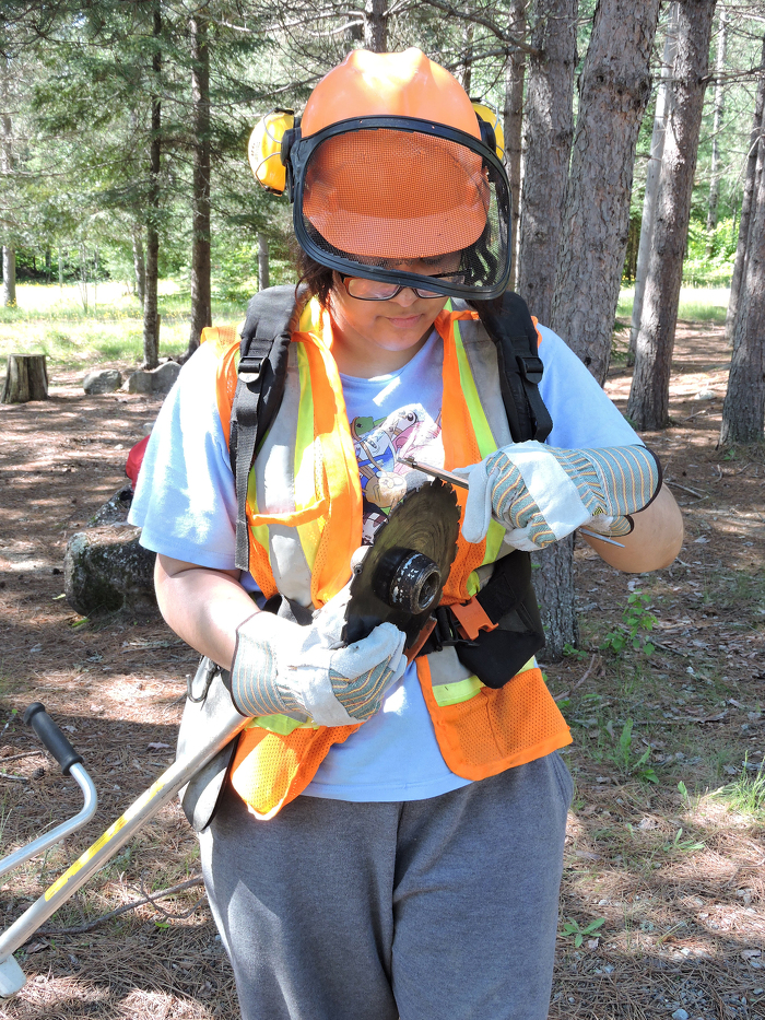 A program participant sharpens her brush saw blade during a restoration project for Quetico park.