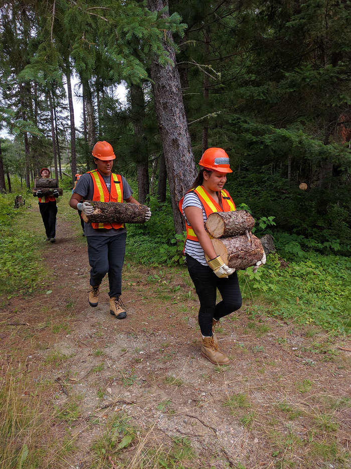 MLFNYEP youth carry recently cut firewood during a course at Mink Lake Camp.
