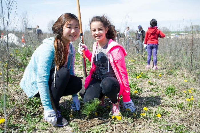 Ontario youth take part in community tree planting event.