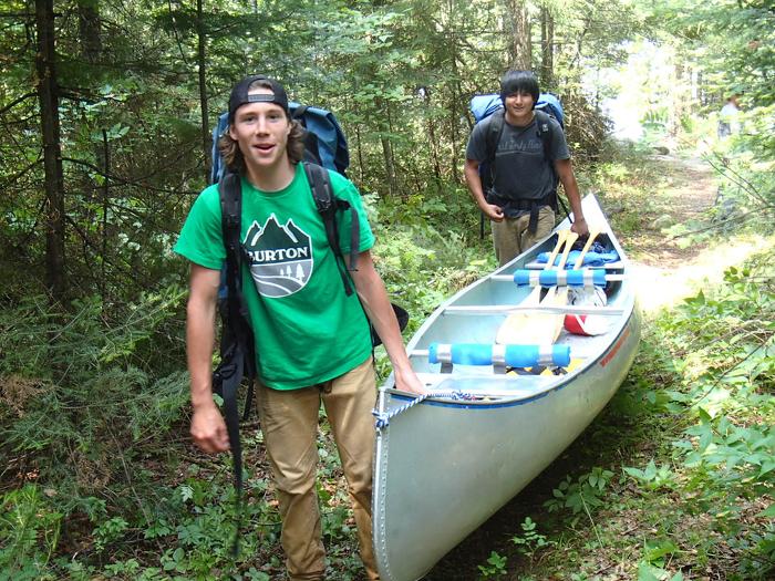 Jeunes brigadiers d'intendance environnementale de Fort Frances en portage avec leur canot dans le cadre de leur travail de restauration de pistes historiques de canotage.