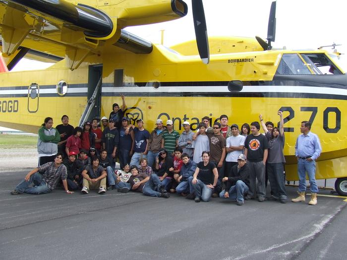 Jeunes du PEJPNRN à côté d'un bombardier à eau du MRNF.