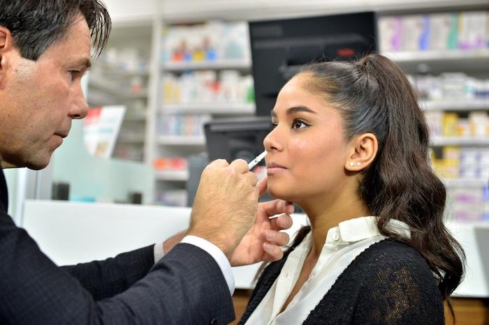 Minister Hoskins administering a nasal spray flu vaccine.