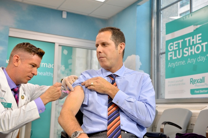 Pharmacist injecting the flu vaccine to Paul Dale of Rexall.