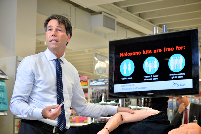 Minister Hoskins demonstrating how to use a naloxone kit.