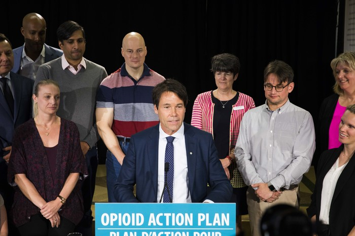 Minister Hoskins speaking at an event, with clinicians, harm reduction workers, people with lived experience and Community Health Centre outreach workers behind him.