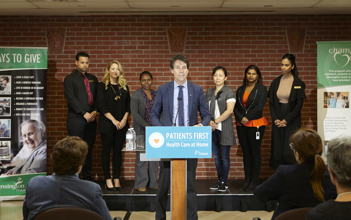 Minister Hoskins speaking at a podium with Kensington Health staff.