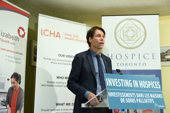 Minister Hoskins speaking at a podium.
