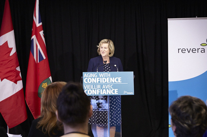 Minister Jaczek speaking at a podium.