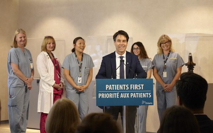 Le ministre Hoskins fait une déclaration à un podium en compagnie de membres du personnel de Sinai Health System.