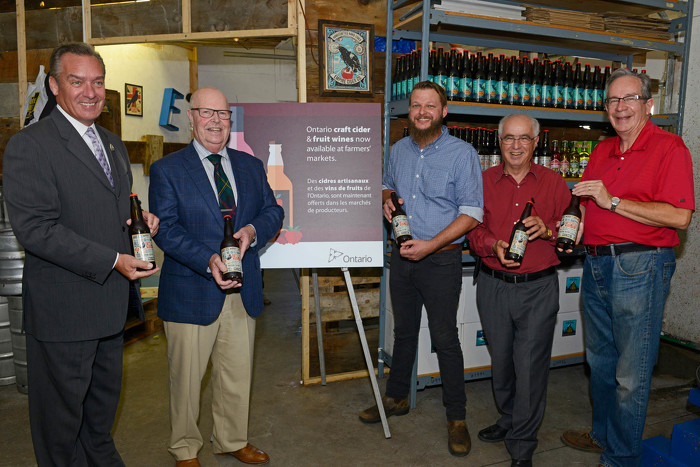 Minister of Agriculture, Food and Rural Affairs, Jeff Leal (right), in Codrington, Ontario with Lou Rinaldi, MPP for Northumberland-Quinte West, Chris McRae, owner of Empire Cider Co.,  Gil Brocanier, Mayor of Cobourg and Mark Walas, Mayor of Brighton (left).
