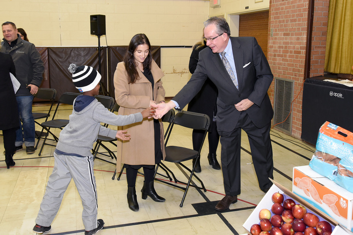 Jeff Leal, Minister of Agriculture Food and Rural Affairs hands an apple to Ahmed Abbass, student of Perth Ave Jr. Public School.