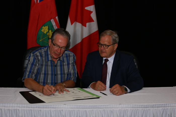 Ontario Minister of Agriculture, Food and Rural Affairs Jeff Leal (left) signs a certificate to support the April 2018 launch of the Canadian Agricultural Partnership, as Agriculture and Agri-Food Canada Minister Lawrence MacAulay looks on. The photo was taken in St. John's, Newfoundland and Labrador, on July 21, 2017, during the Annual Meeting of the Federal, Provincial and Territorial Ministers of Agriculture.