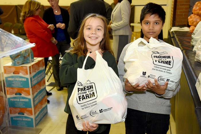 Arden Charnock et Theo Mukhatee, deux élèves à la Perth Avenue Junior Public School, avec leurs sacs de fruits et légumes du programme Fraîcheur de la ferme.