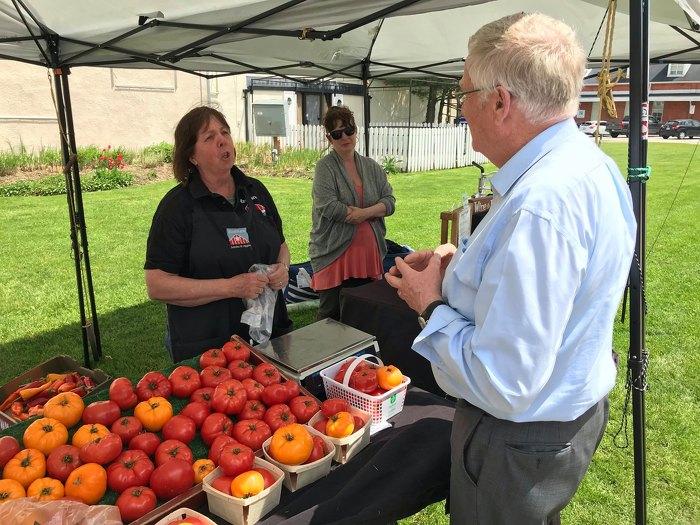 Le ministre de l'Agriculture, de l'Alimentation et des Affaires rurales, M. Ernie Hardeman, visite le marché de producteurs de Woodstock et s'entretient avec des commerçants de l'entreprise RedBarn Berries & Veggies au sujet de l'importance des occasions de vente directe.
