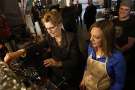 L'Ontario augmente le salaire minimum Image: La première ministre Wynne fait une annonce concernant le salaire minimum en compagnie de l'honorable Yasir Naqv, ministre du Travail, au Coffee Pub de Toronto.